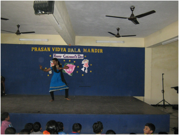 A teacher dancing enthusiastically for a traditional dance.